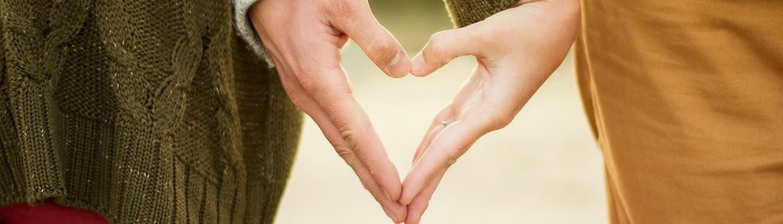 זוג עושים לב עם הידיים שלהם