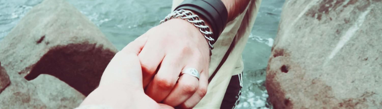 גבר מחזיק יד של אישה, עוזר לה לרדת לים