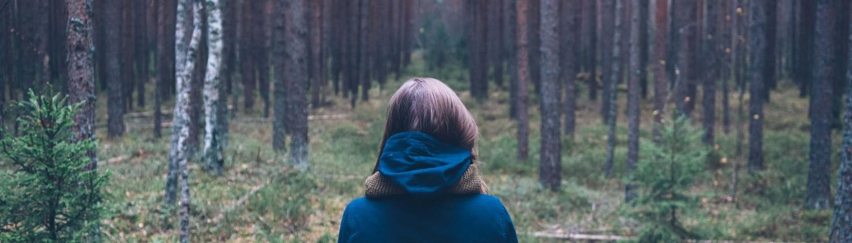 אישה עומדת באמצע יער סמוך