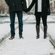 זוג מחזיקים ידים על פסי הרכבת בשלג