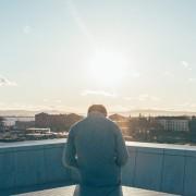 גבר יושב על קצה בניין ומסתכל על הנוף